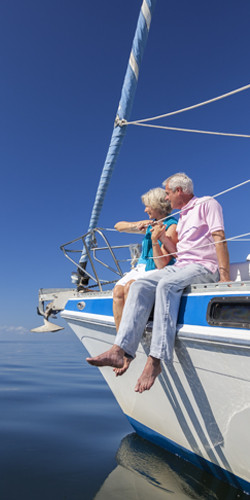 Older couple sitting on their boat, looking out over the water