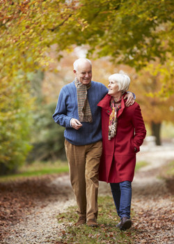 Retired couple walking along a trail through a park